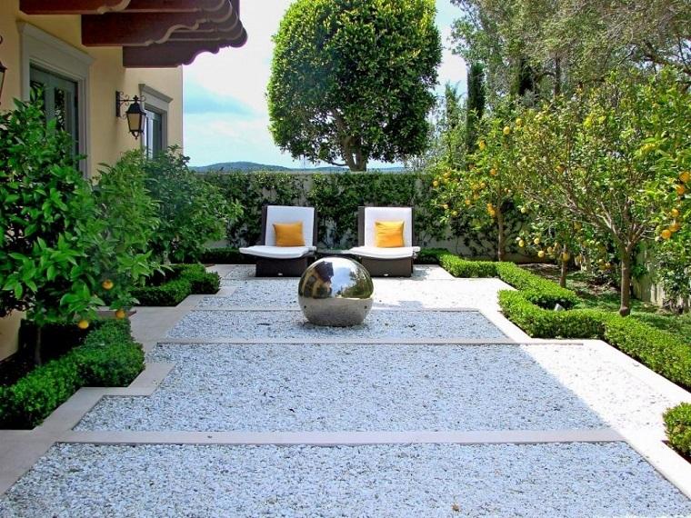 Idee per il giardino, pavimentazione con ghiaia, arredo con due sdrai e decorazione con una palla di metallo