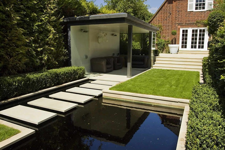 Idee per il giardino, piccolo laghetto artificiale con lastre di cemento per passare, prato verde e mobili da esterno