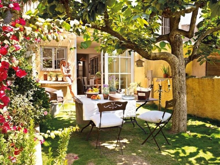 Come arredare i piccoli giardini di villette con mobili in ferro battuto e rattan, prato verde e un albero