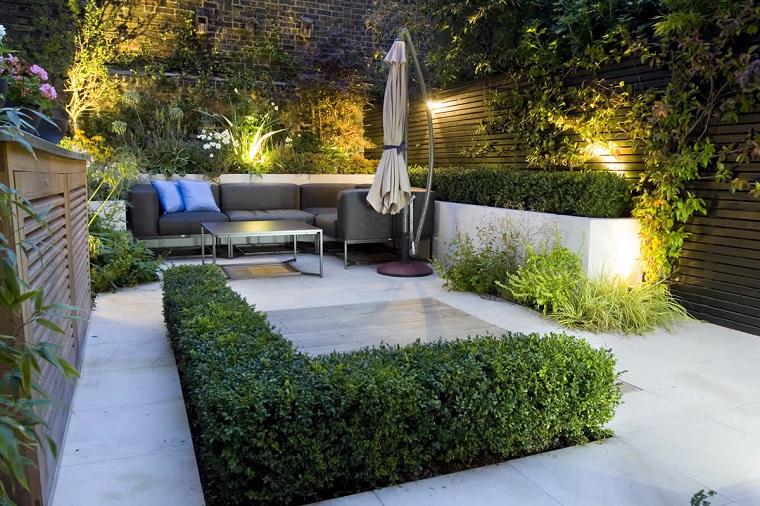 Giardini immagini, arredamento con un divano di colore grigio e tavolino, recinzione in legno e decorazione con siepe