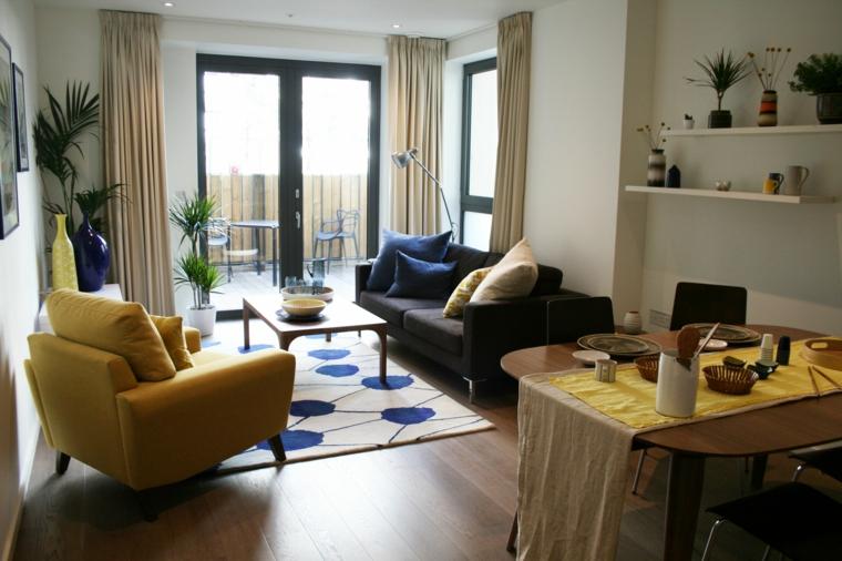 stanza rettangolare open space arredata con divano scuro, poltrona gialla e tavolo ovale in legno