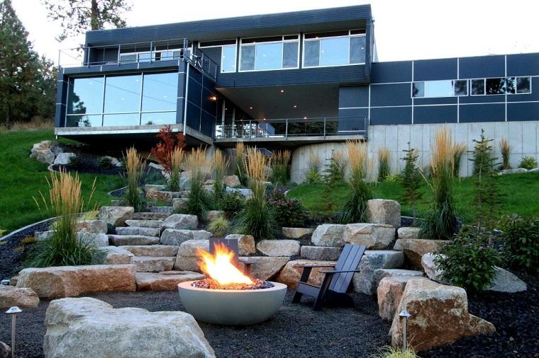 Giardini da copiare, casa moderna con tanti vetri, area esterna con camino moderno e pietre molto grandi