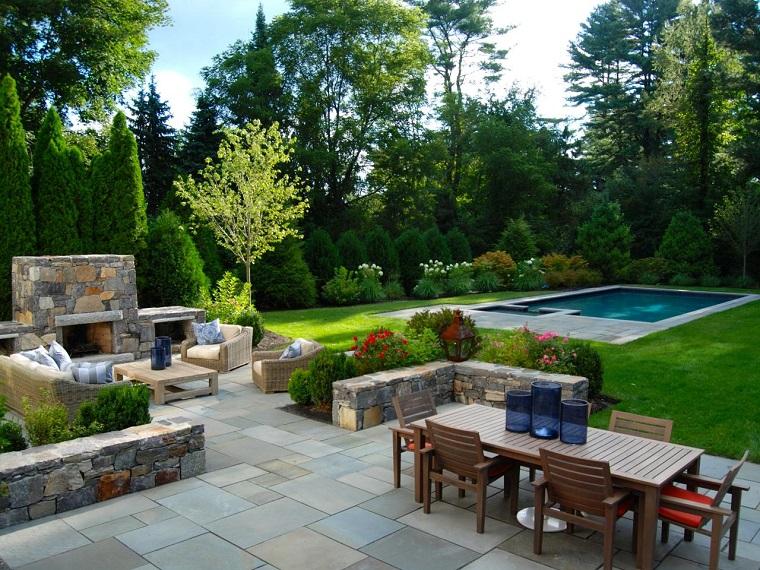 Idee giardino, prato verde con piscina e arredamento con mobili in legno, camino da esterno in muratura