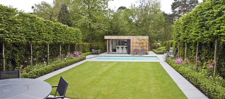Siepe molto alta e un giardino con piscina, casetta con zona bar e un tavolo rotondo da esterno