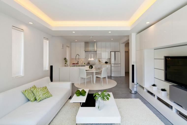 open space arredato quasi totalmente in bianco con un divano lineare e tavolino da caffè rettangolare