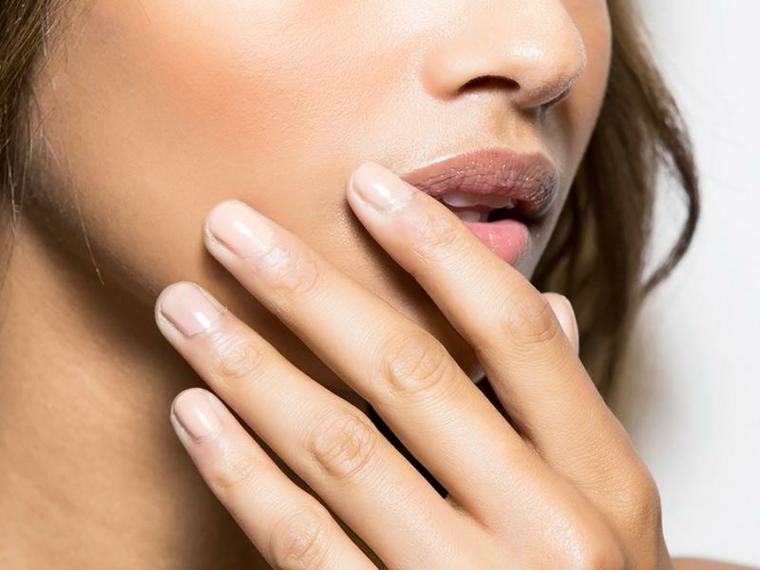 esempio di nail art color carne su unghie corte e squadrate, ragazza castana con labbra carnose