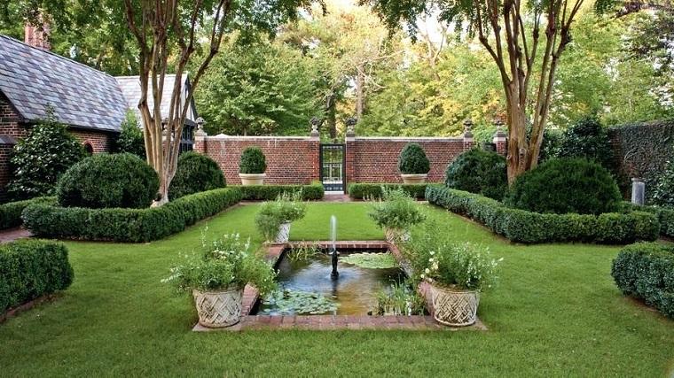 Laghetto artificiale con fontana e piante in vasi, siepe e una recinzione con muro in pietra