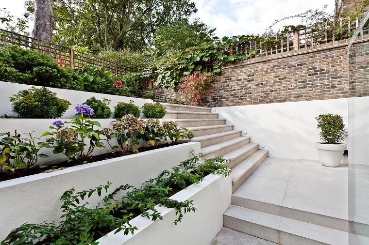 Idee per il giardino, recinzione con muro e ringhiera in ferro, piante a più livelli