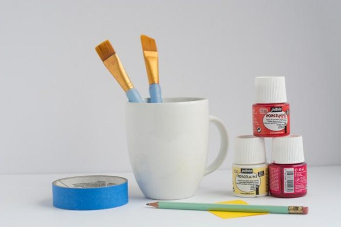 materiale per cose da creare in casa ideali come regali natalizi fai da te, tazza bianca, pennelli, colori, matita