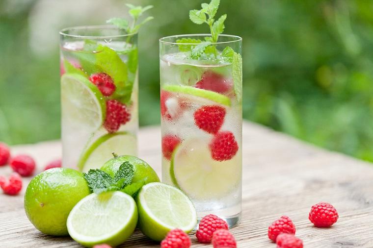 Una bevanda detox fai da te a base di acqua, lamponi e pezzettini di lime