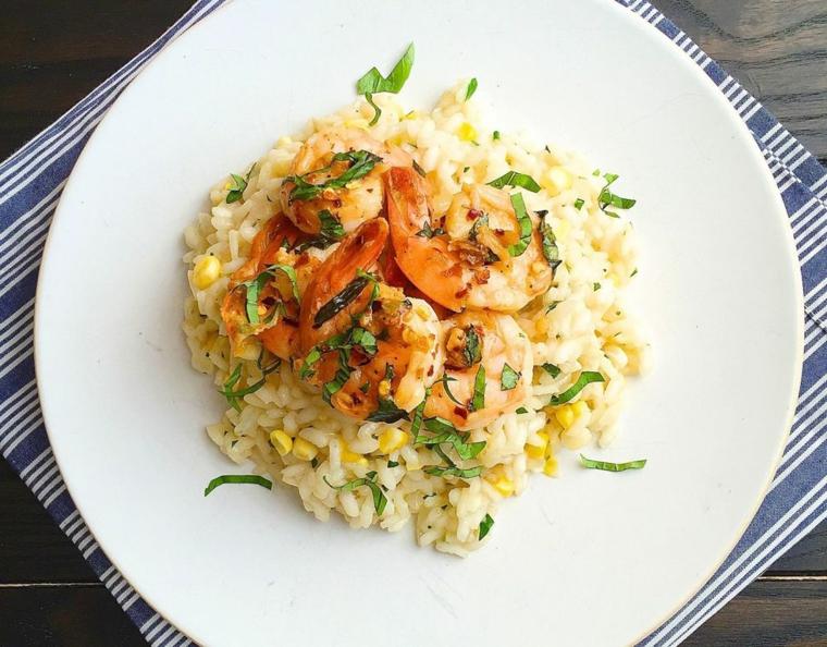 Idee per cena, risotto ai frutti di mare con prezzemolo tritato e mais