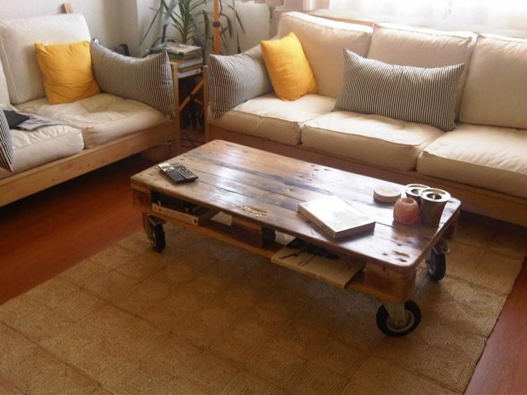 soggiorno arredato con due divani in legno con cuscini color panna e un tavolo con pallet