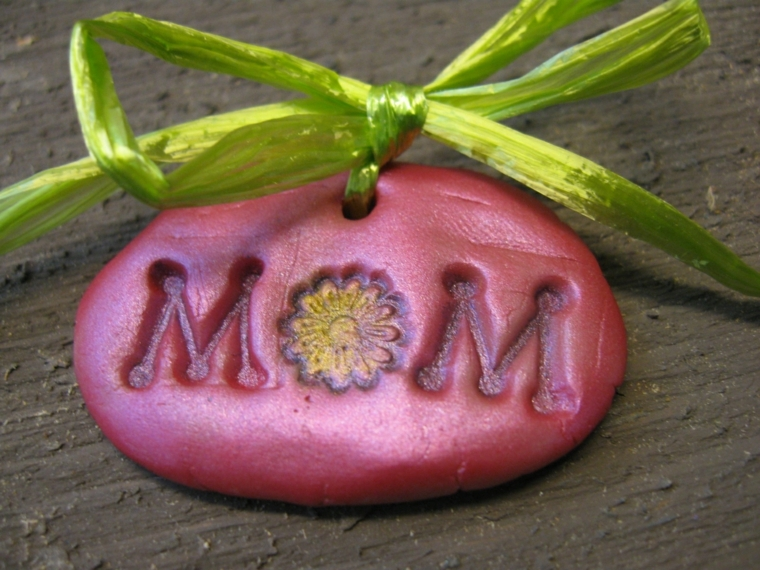 idea per dei lavoretti facili, un sasso decorato con la scritta mamma e un fiocco