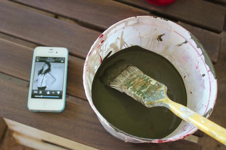 tavolo con appoggiati un cellulare, un secchio con la pittura e un pennello per dipingere il divano pallet