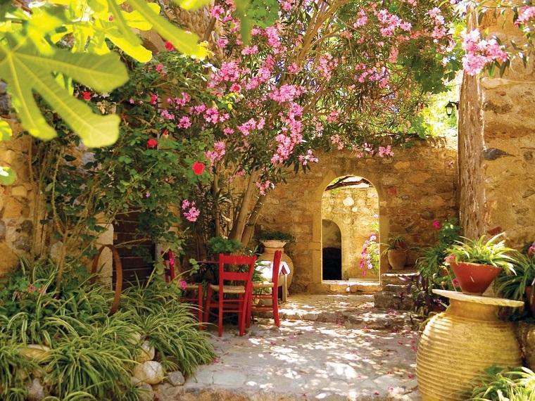 Idee giardino, arredamento con sedie di colore rosso e muri in pietra, fiori e alberi come decorazione