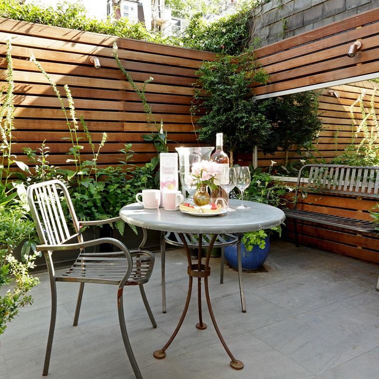 Giardini idee da copiare, tavolo rotondo e sedia in ferro battuto, recinzione alta in legno
