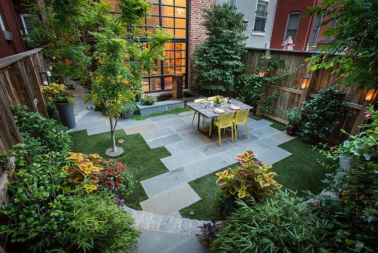 Un piccolo giardino all'ombra con alberi e tante piante sempreverdi, arredamento con mobili in legno di colore giallo