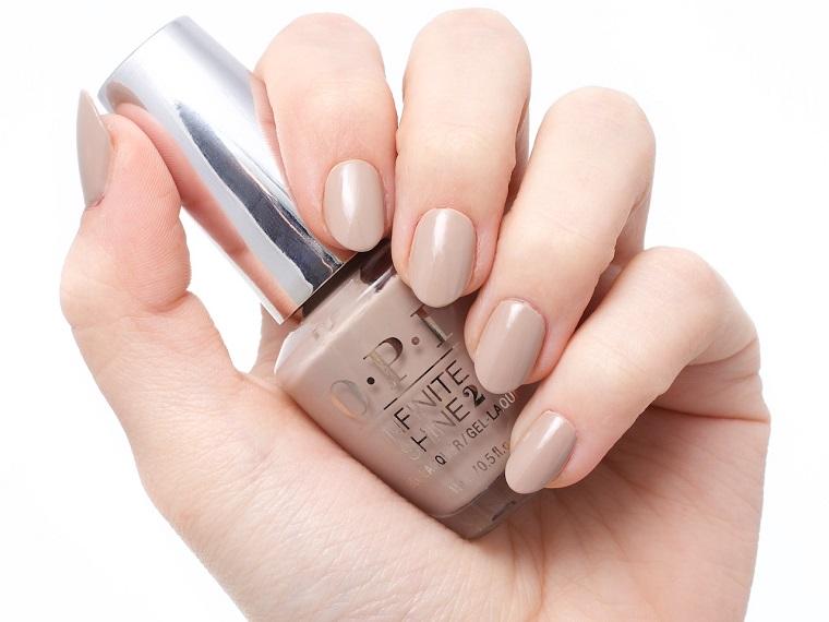 Unghie belle di colore nude, smalto del marchio OPI, mani donna eleganti