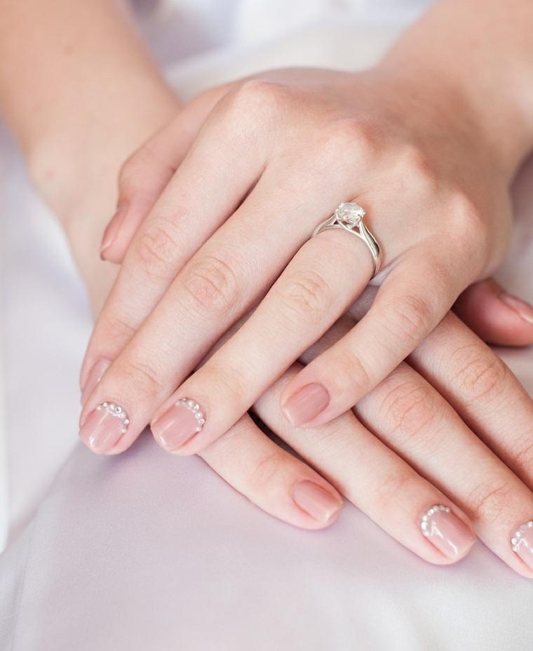 Fede sposa in oro bianco con diamante, unghie sposa corte colore nude con brillantini