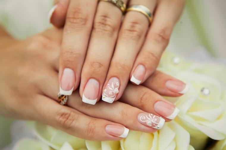 Unghie belle, decorazione della french manicure con fiorellini e piccolo brillantino, mani da sposa