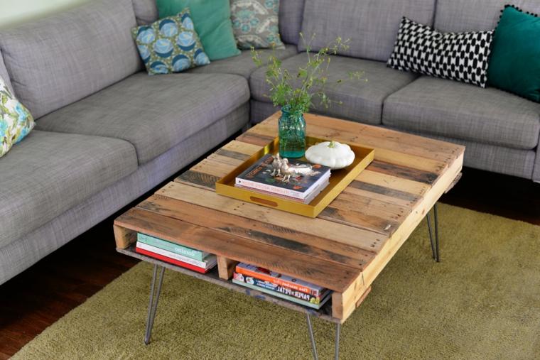 salotto arredato con un divano angolare grigio, un tappeto e un tavolo con pallet