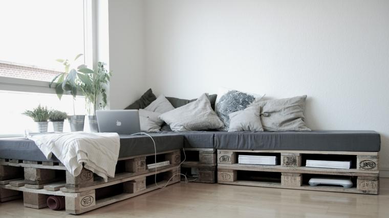 zona soggiorno arredata con dei divani con bancali con cuscini grigi chiari e scuri