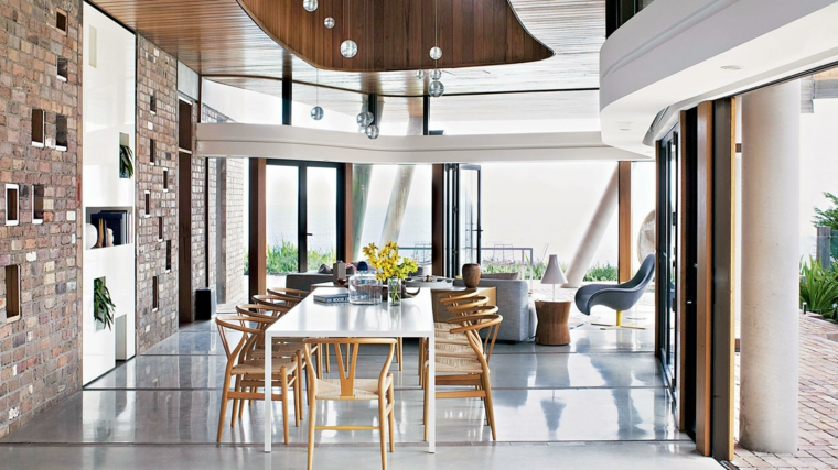 proposta per arredare soggiorni moderni con una zona per il pranzo, parete con mattoni a vista e vetrate