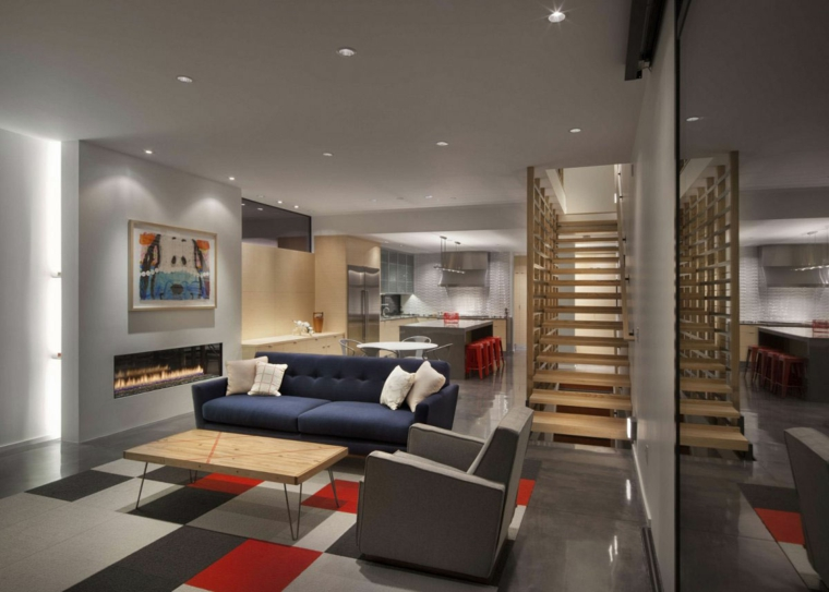 ampia stanza aperta con soggiorno con camino moderno e zona pranzo con ampio tavolo e sgabelli rossi