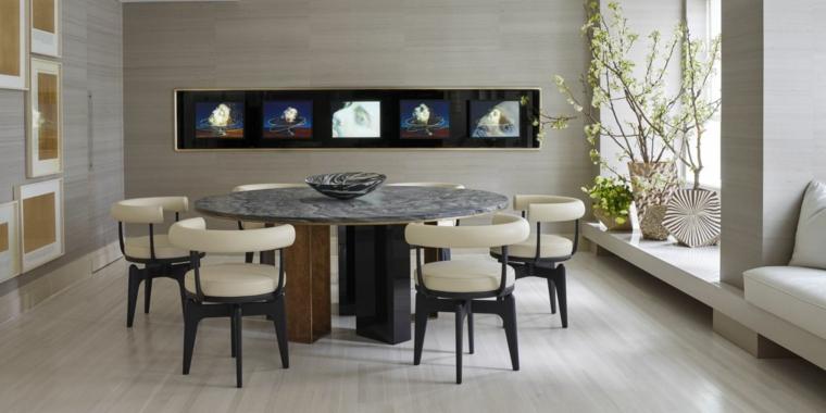 stanza ampia e moderna con un grande tavolo rotondo per il pranzo e divani e tv a parete