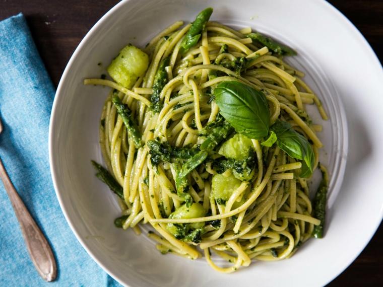Idee per cena, spaghetti al pesto genovese e patate cotte, foglie di basilico come decorazione