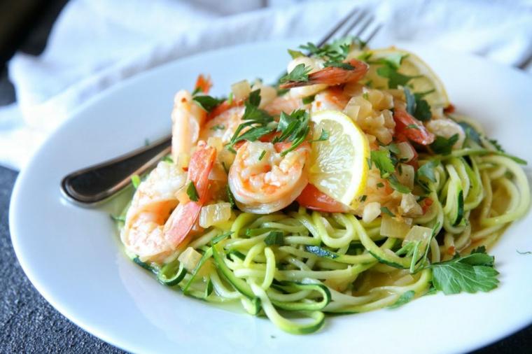 Cosa cucinare per cena, spaghetti alle zucchine e scampi, condimento con del prezzemolo tritato