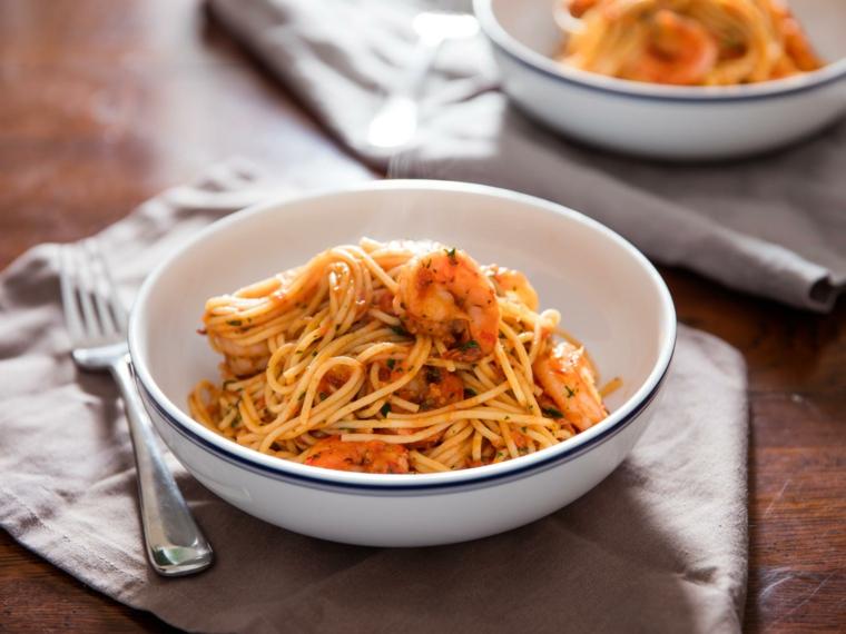 Secondi piatti semplici e gustosi, spaghetti al sugo e scampi, condito con del prezzemolo tritato