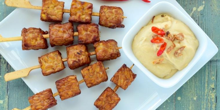 piatto gustoso e sfizioso con degli spiedini di tufo e della salsa, tofu ricette giallo zafferano