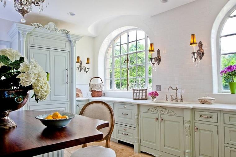 ampia cucina shabby chic provenzale con mobili bianchi e tavolo in legni, vasi con fiori