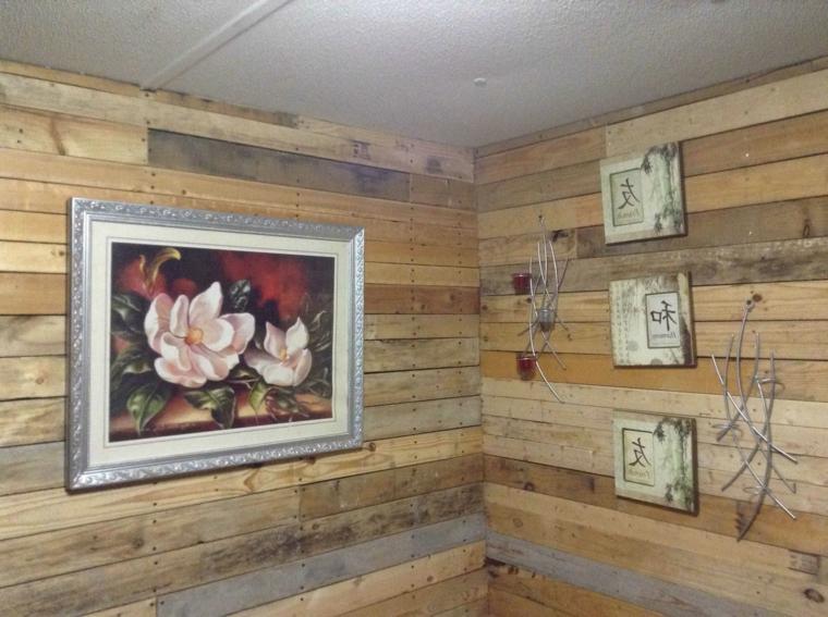 pareti di una piccola stanza ricoperte con delle assi di legno dei bancali, quadri e decorazioni in alluminio