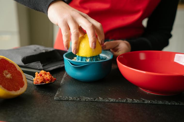 Donna che spreme un mezzo limone, come cucinare il tofu, ciotola di porcellana di colore rosso