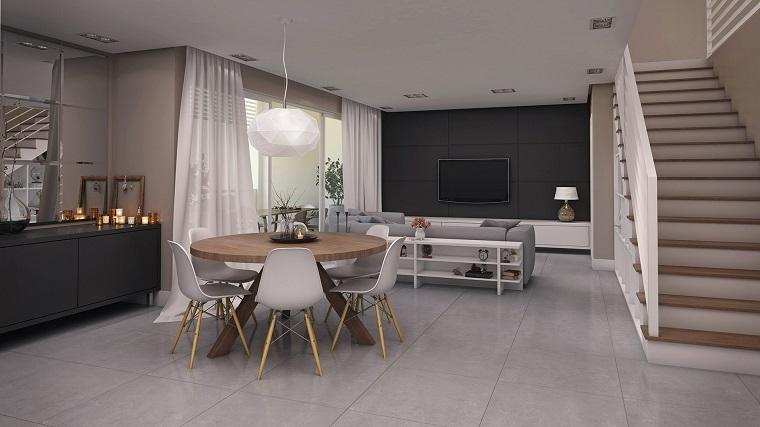 Cucina soggiorno open space, tavolo da pranzo in legno con sedie bianche, parete nera con tv appesa