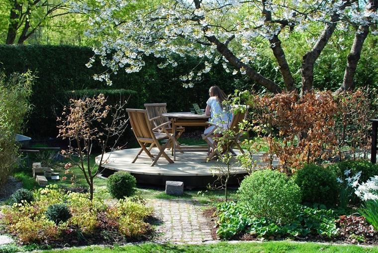 Giardino con alberi in fioritura e un arredamento con mobili da esterno in legno