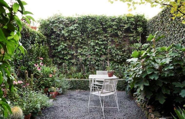 Piante rampicanti sulla recinzione del giardino, tavolino e due sedie in ferro battuto