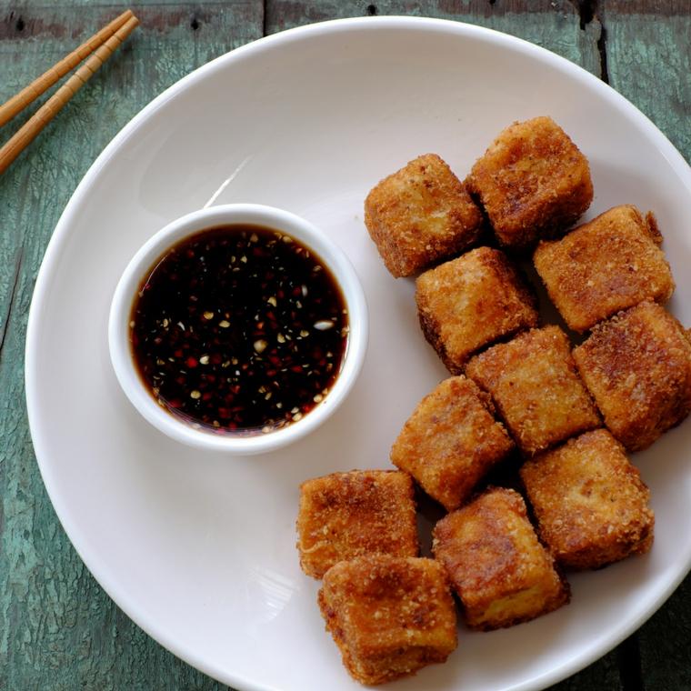 cubetti di tofu croccanti accompagnati con una salsa agrodolce e sesamo