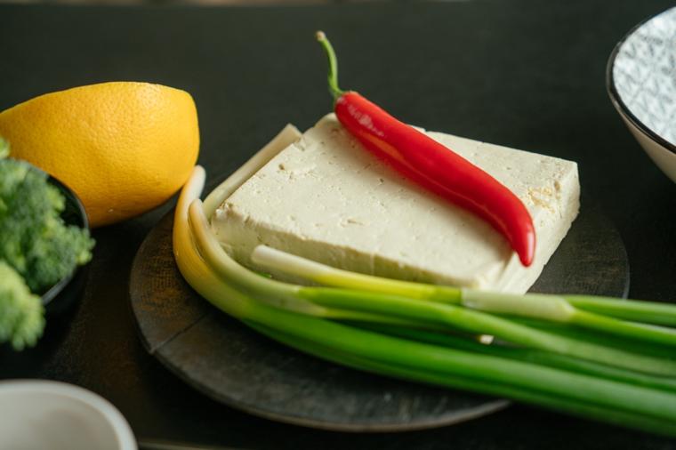 Come cucinare il tofu, piatto con tofu e un peperoncino rosso, mezzo limone e cipolla verde