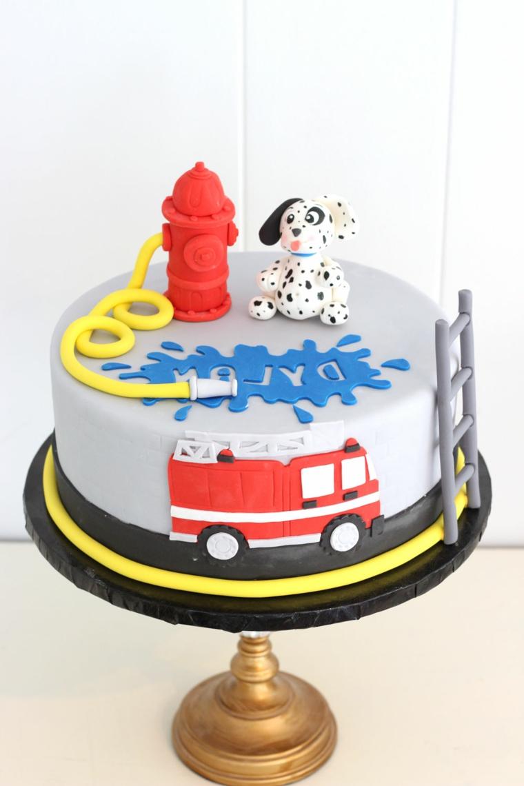 Torte per bambini, una dalla forma rotonda con un cagnolino e camion dei pompieri