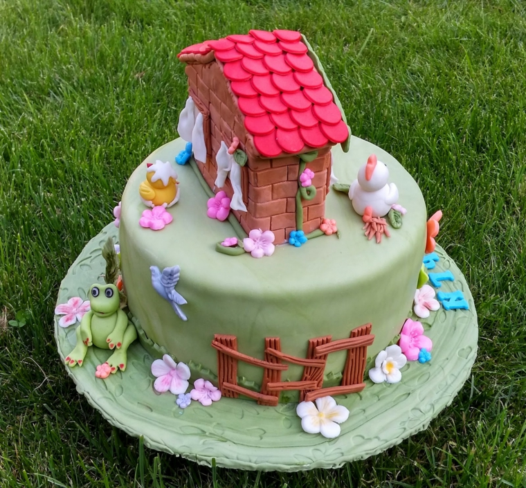 Una torta decorata e poggiata sull'erba, torte semplici e gustose decorate con pasta di zucchero