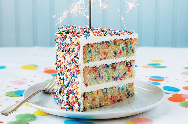 Pezzo di torta con strati colorati, torte di compleanno semplici con crema bianca e candela