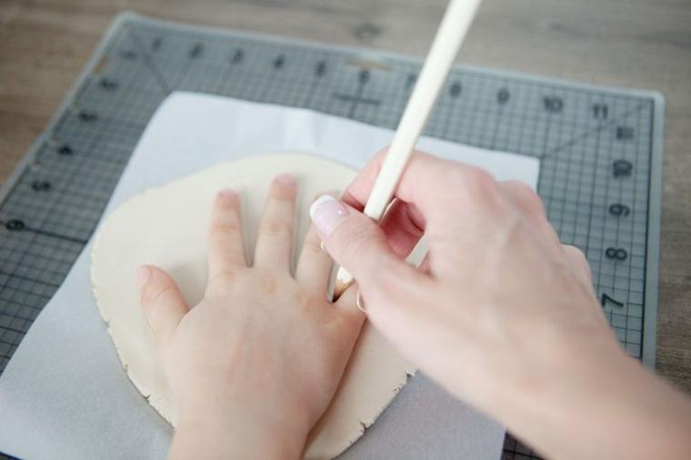disegnare la sagoma della mano del bambino sull'argilla con una matita, lavoretti creativi festa della mamma