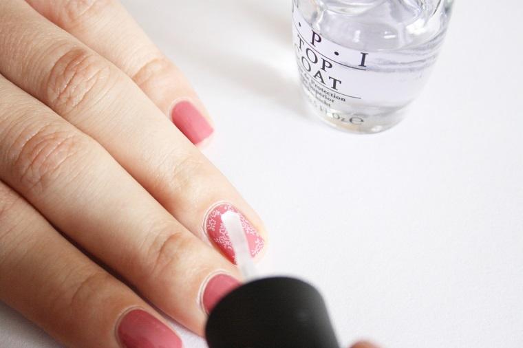 Top coat trasparente da applicare sulla manicure, unghie belle di colore rosa, accent nail effetto pizzo