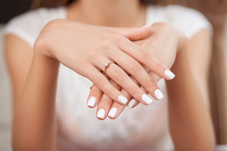 Mani sposa con smalto di colore bianco, unghie bellissime, fede in oro con piccolo diamante