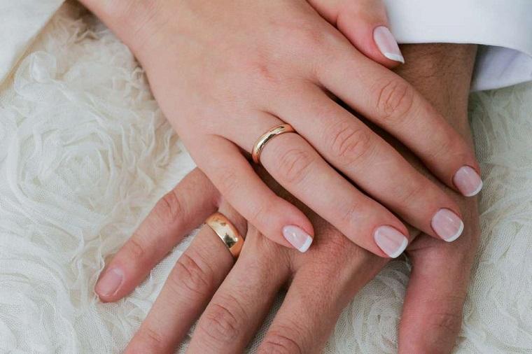 Mani uomo e donna una sopra l'altra, unghie gel semplici ma belle, french bianco su una base rosa chiaro