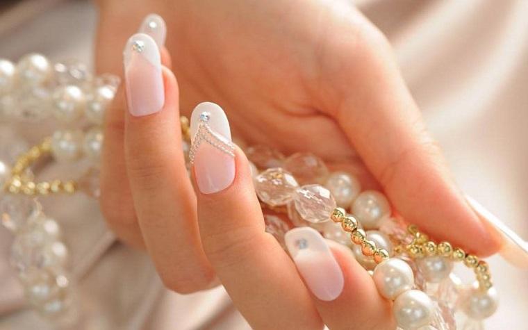 Idea per delle unghie gel bianche brillantini, manicure a mandorla. collana di perle in mano di una donna
