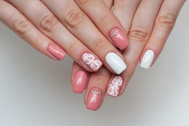 Decorazioni unghie rosa cipria con fiorellini e brillantini, accent nail di colore bianco gel